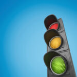 Closeup of traffic lights against blue sky background
